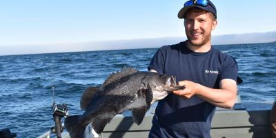 person holding a black rockfish